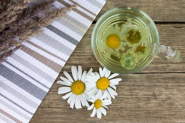 Copo de vidro transparente de chá de camomila em fundo de madeira vintage com ervas secas e margarida