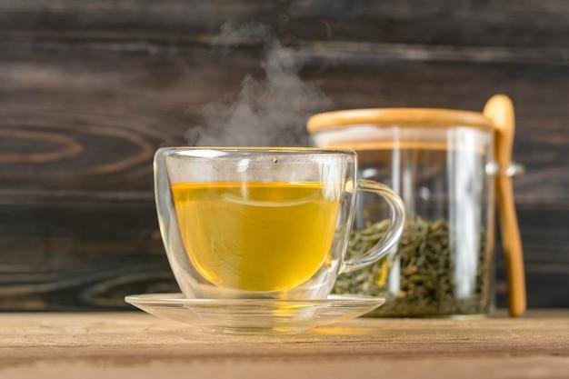 Copo de vidro transparente de chá verde quente com vapor e lata com folhas de chá e colher na mesa de madeira bebida saudável, conceito de bebida anti-stress