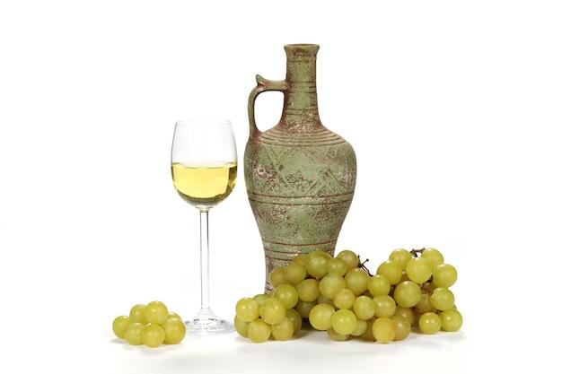 Copo de vinho branco ao lado de uma jarra de vinho com uvas verdes em um branco