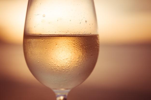 Copo de vinho branco ao pôr do sol com céu dramático