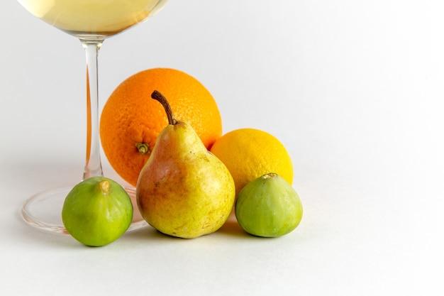 Copo de vinho branco com frutas frescas em uma mesa branca leve beber álcool barra de frutas de água