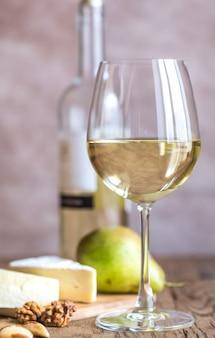 Copo de vinho branco com queijo e nozes