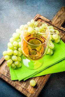 Copo de vinho branco com um ramo de uvas