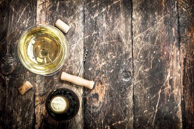 Copo de vinho branco com um saca-rolhas. em uma mesa de madeira.