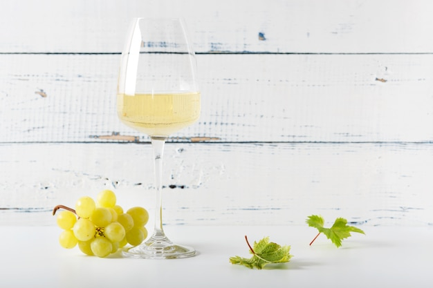 Copo de vinho branco na mesa de madeira vintage.