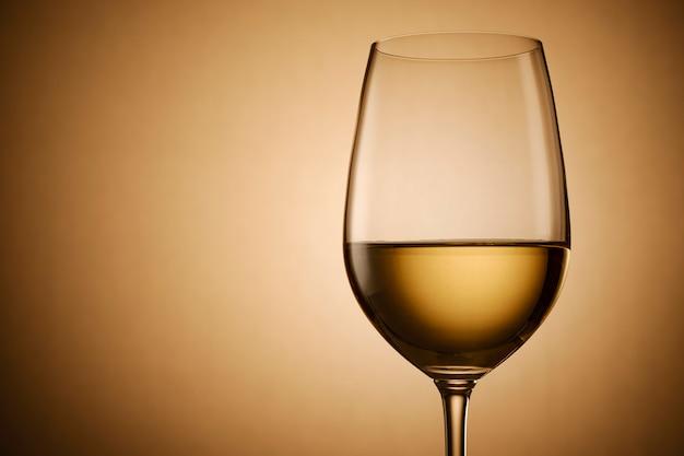 Copo de vinho branco no gradiente de ouro