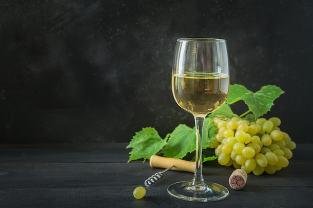 Copo de vinho branco, uva madura na mesa de madeira preta.