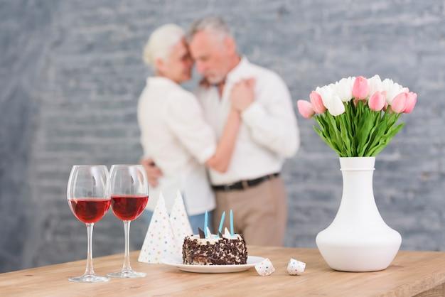 Copo de vinho; chapéu de festa; bolo de aniversário e vaso de flor na mesa na frente turva casal dançando