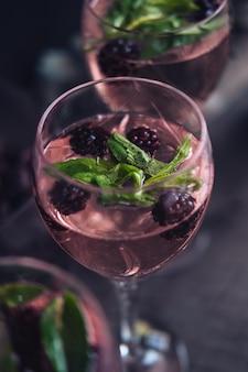 Copo de vinho cheio de líquido com amoras e folhas
