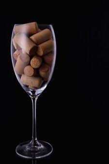 Copo de vinho cheio de rolhas de vinho sobre fundo preto