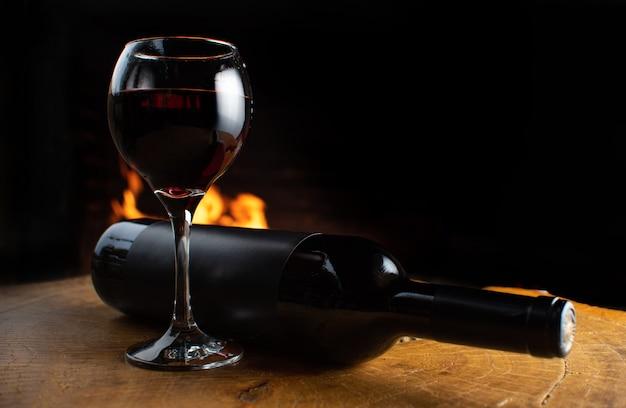 Copo de vinho cheio e garrafa de vinho sobre uma superfície de madeira rústica com fogo atrás