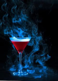 Copo de vinho com bebida vermelha e fumaça