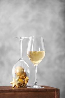 Copo de vinho com brinquedos de natal na superfície da parede cinza
