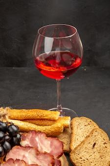 Copo de vinho com pãezinhos e pão na foto de cor escura com álcool.