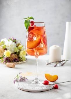 Copo de vinho com pêssegos e hortelã