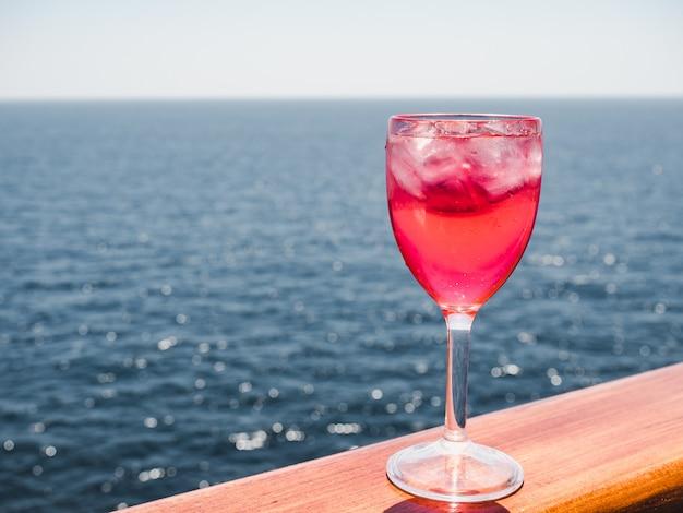 Copo de vinho com um cocktail rosa e cubos de gelo