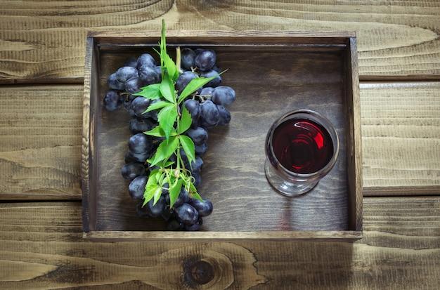 Copo de vinho com vinho tinto e a uva madura na placa de madeira.