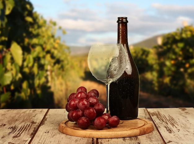 Copo de vinho com vinho tinto, garrafa de vinho e uvas