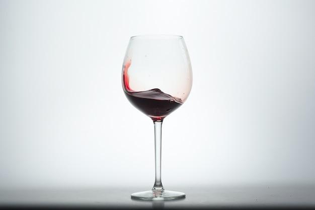 Copo de vinho com vinho tinto no fundo branco