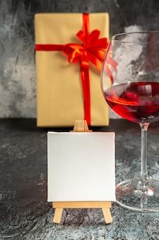 Copo de vinho com vista frontal e tela branca em cavalete de madeira no escuro