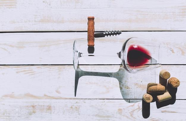Copo de vinho, cortiça e saca-rolhas sobre a mesa de madeira