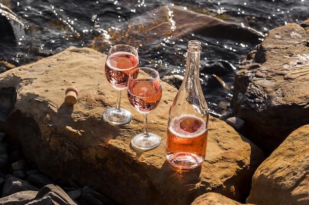 Copo de vinho de alta vista e garrafa nas rochas do oceano