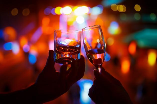 Copo de vinho de champanhe na mão da mulher e um copo de uísque em uma mão de homem