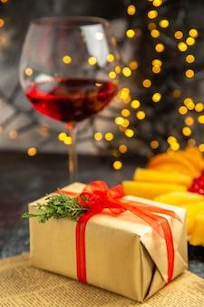 Copo de vinho de frente para presente de natal nas luzes escuras