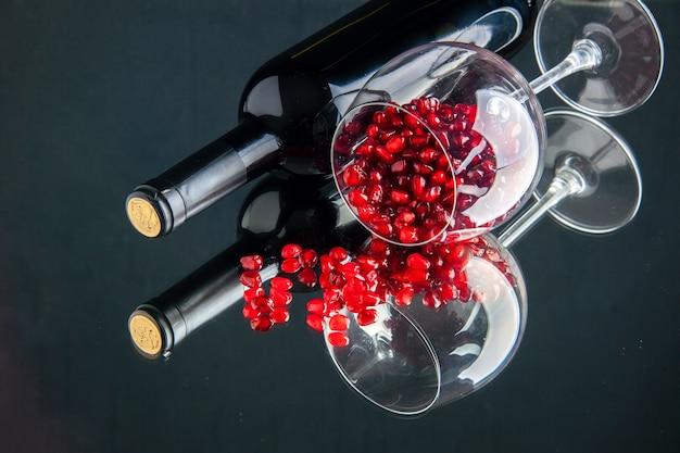 Copo de vinho de vista frontal com romãs descascadas na superfície escura