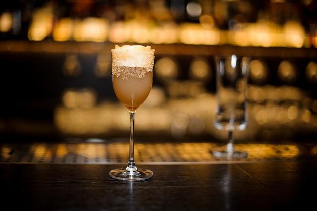 Copo de vinho doce cheio de delicioso coquetel de brandy azedo crusta no balcão do bar