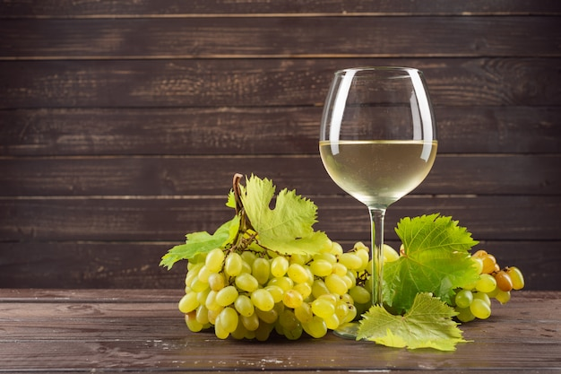 Copo de vinho e cacho de uvas na mesa de madeira