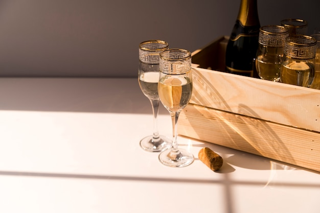 Copo de vinho e champanhe em caixa de madeira na mesa branca