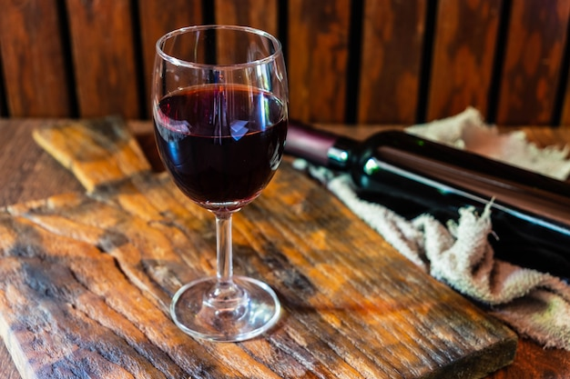 Copo de vinho e garrafa de vinho na mesa de madeira