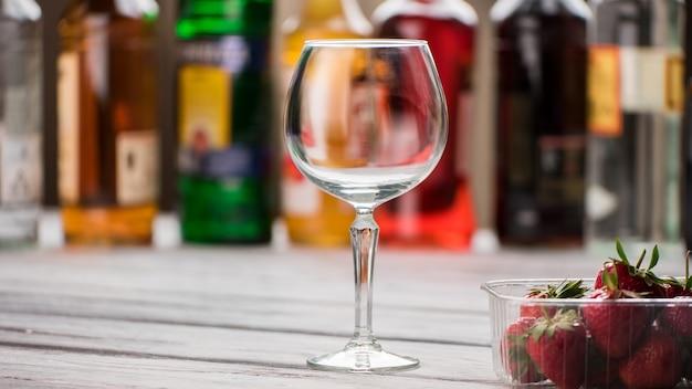 Copo de vinho e morangos vazios. bagas em um recipiente. mesa de madeira no bar. quem quer beber.