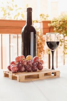 Copo de vinho e uva em uma mesa de madeira branca