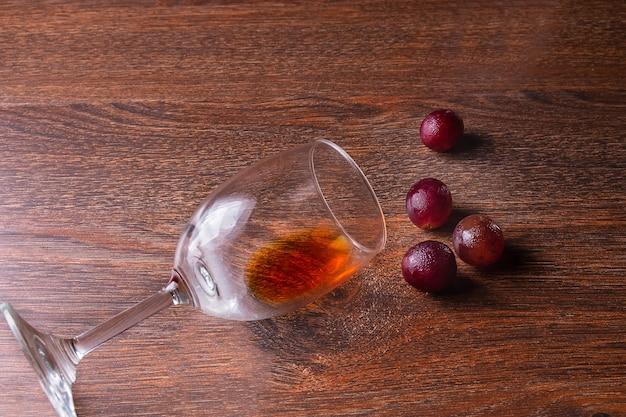 Copo de vinho e uvas vermelhas em um fundo de madeira.