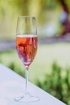 Copo de vinho espumante rosa ao ar livre comemorando o conceito de viagens relaxantes