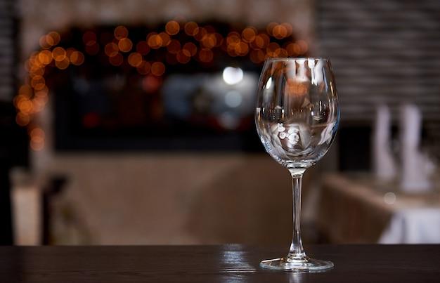 Copo de vinho limpo vazio com reflexão em um fundo borrado com bokeh.