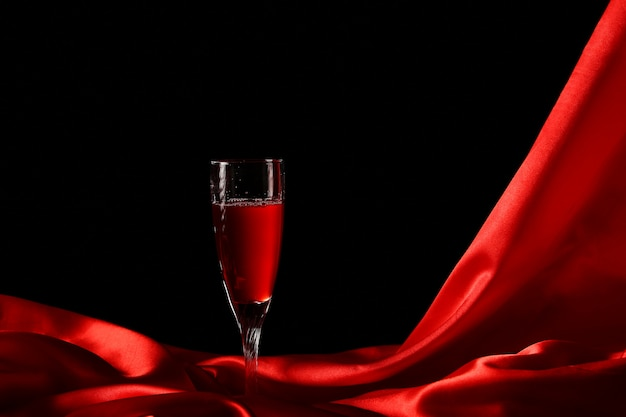 Copo de vinho na seda vermelha com fundo escuro