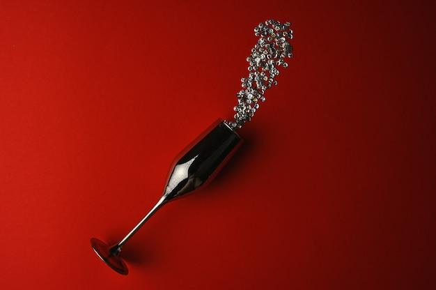 Copo de vinho no espaço vermelho com confete. foto de alta qualidade