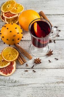 Copo de vinho quente com laranja e canela de anis na mesa de madeira branca com copyspace