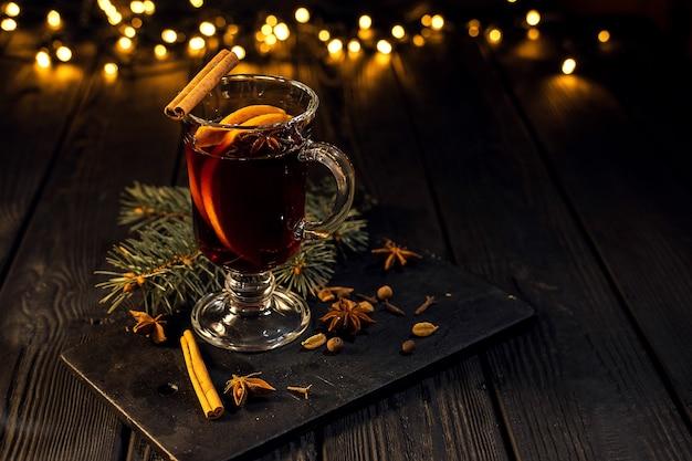 Copo de vinho quente com laranja e canela em fundo preto escuro