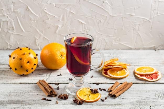 Copo de vinho quente delicioso com canela de anis de laranjas na mesa de madeira branca
