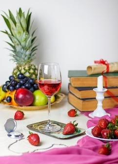 Copo de vinho rosé na mesa de madeira branca com livros antigos e relógio, diferentes frutas tropicais e morangos