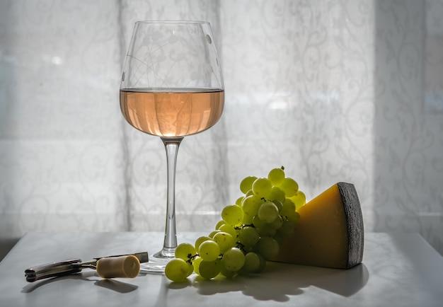 Copo de vinho rosé na mesa em dia de sol, ao lado de uvas verdes, queijo duro, saca-rolhas com cortiça. close-up, luz de fundo, orientação horizontal