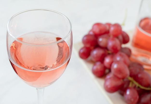 Copo de vinho rosé, uvas e garrafa.