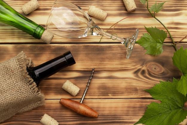 Copo de vinho, saca-rolhas, rolhas, garrafas de vinho, videira sobre fundo rústico de madeira queimada. vista do topo. copie o espaço