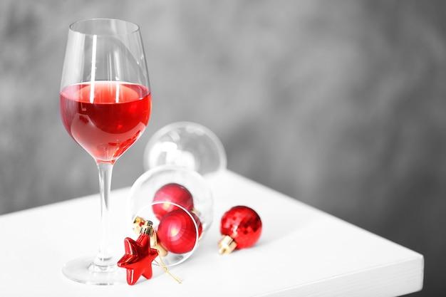 Copo de vinho tinto com acessórios de natal no fundo cinza da parede