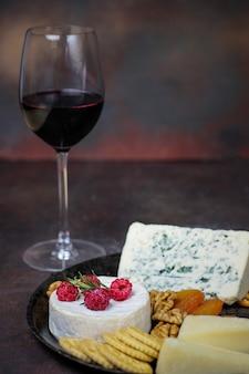 Copo de vinho tinto com prato de queijo no escuro com queijo camembert, queijo azul, gauda e frutas e lanches