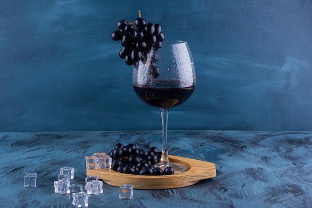Copo de vinho tinto com uvas pretas na mesa de mármore.